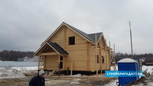 Строительная бригада возводит деревянный дом